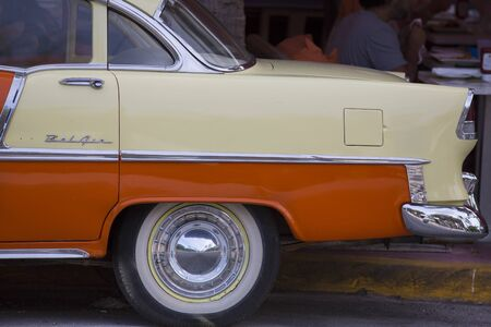 hubcap: Close-up of an old orange car in Miami Editorial