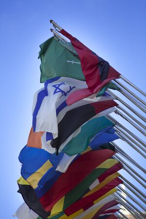 Group of flags of many different nations against blue sky Stock Photo