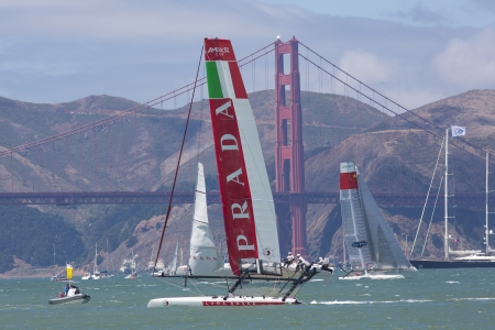 overtake: SAN FRANCISCO, CA - AUGUST 26: Chinese team tries to overtake the Italian team in front of the Golden Gate Bridge in the bay of San Francisco during the final of the Americas Cup 2012.