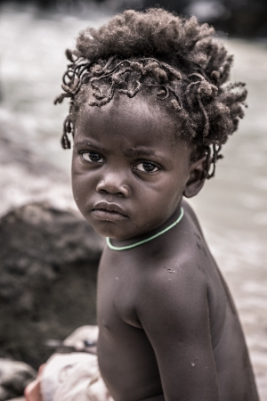 nomadic: NAMIBIA,KUNENE, JANUARY 7  portrait of a young kid of the Himba people looking at the camera  The Himbas are indigenous people living in northern Namibia, in the Kunene region  formerly Kaokoland  and on the other side of the Kunene River in Angola, Janua