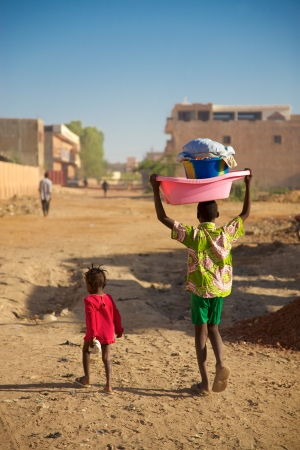 MALI, MOPTI, DECEMBER 28: Unidentified Small kid walking in the street with his brother early in the morning carrying laundry on his head in Mopti, 2010