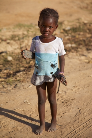 poorness: MALI, MOPTI, DECEMBER 28: Unidentified Young girl with her shoes in her hands in Mopti early in the morining.2010, Mali