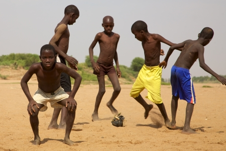 SENEGAL, SAINT LOUIS, DECEMBER 17: Unidentified Kids playing soccer with a home made ball, created with clothes, one kid is looking at the camera and the other are playing