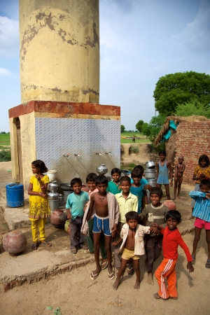 INDIA, AGRA, JUNE 18: Group of unidentified children posing in front of a Water point. A Fair trade Pushpanjali project in India, 2010