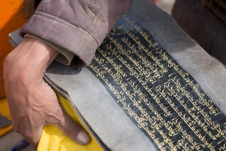 모든 티베트어 언어의 신성한 티베트어 텍스트와 그것을 운반하는 스님의 손을 포함하여 오래 된 책.