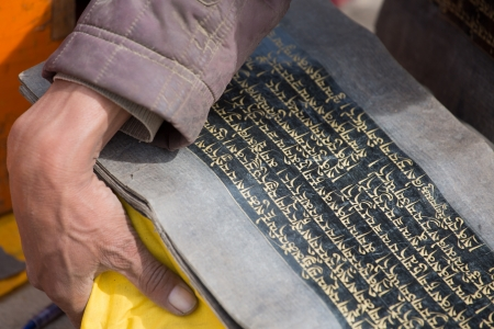 linguistic: Old  book including all the sacred Tibetan text in Tibetan language and the hand of a monk carrying it. Stock Photo