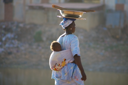 cultural and ethnic clothing: MALI, MOPTI, DECEMBER 28  Unidentified Woman carrying a baby in her back in the streets of Mopti  2010
