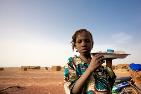 MALI, DJENNE, JANUARY 1  Unidentified Girl selling food and water on the road to Mopti, she looks tired and has probably spent the entire day trying to earn maximum a dollar a day, Mali, 2011