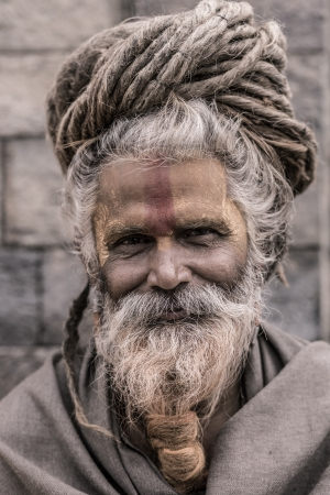 NEPAL, KATHMANDU, APRIL 24: Portrait of an Holy Sadhu man with traditional painted face, praying in Pashupatinath Temple in Kathmandu, Nepal. In Hinduism, sadhu is a common term for a mystic, an ascetic, practitioner of yoga and wandering monks. April 24, Stock Photo - 20552320