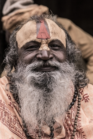 NEPAL, KATHMANDU, APRIL 24: Portrait of an Holy Sadhu man with traditional painted face, praying in Pashupatinath Temple in Kathmandu, Nepal. In Hinduism, sadhu is a common term for a mystic, an ascetic, practitioner of yoga and wandering monks. April 24,