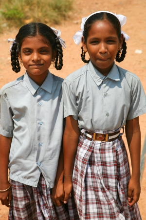 INDIA, VARKALA, OCTOBER 13: Two unidentified sisters walking back from school and posing in front of the camera while they are holding their hands, Kerala,  India.2009