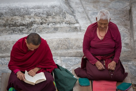 migrated: NEPAL, KATHMANDU, APRIL 21: unidentified Tibetan women monk praying at the Boudhanath Stupa. Since 2008, most of the remaining monks have migrated to Kathmandu, Nepal 2013. Editorial