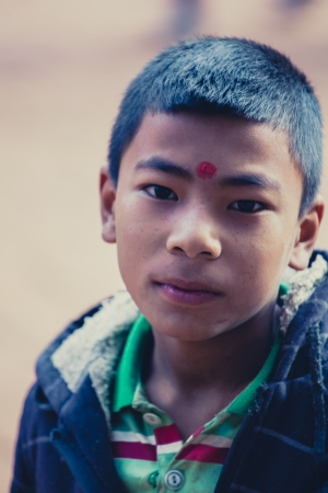 NEPAL, BHAKTAPUR, APRIL 24: unidentified Boy with red dot in the street. The red dot means that he went earlier to the temple, Nepal 2013.