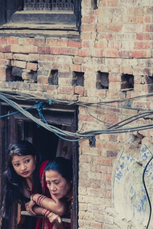 NEPAL, BHAKTAPUR, APRIL 24: Two Traditional unidentified women  looking through the window at a wedding in the street of Bhaktapur 24 april 2013, Nepal.
