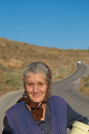 FOLEGANDROS, GREECE, JULY 22  Unidentified old traditional greek woman walking with a sweet smile  Since the start of the Greek crisis, pensions have been reduced drasticaly, Greece 2013