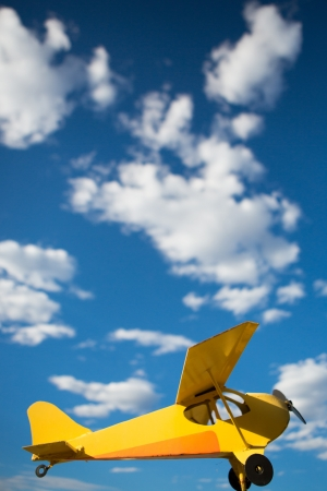 Yellow old airplane against sunny blue sky