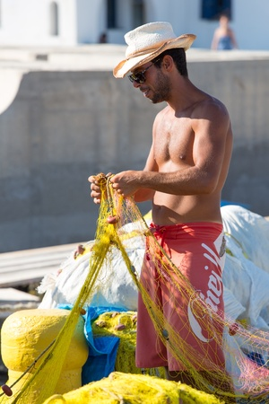 FOLEGANDROS, GREECE, JULY 21: Unidentified Fisher man at work and inspecting his nets in the harbor on the aegean sea in folegandros, Greece, 2013. Stock Photo - 21457183