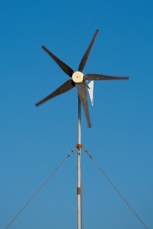 Moving propellor from a little wind turbine in the clear blue sky of folegandros, Greece. photo