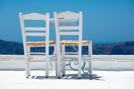 Two white chairs and a blurred panoramic view of the hills of santorini, Greece 2013.