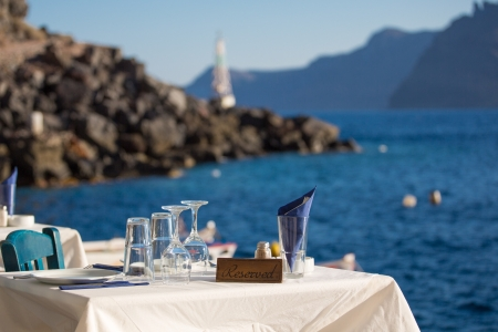 Reserved table in front of the aegean sea, in the blurred background , you see the shore-line of Santorini.