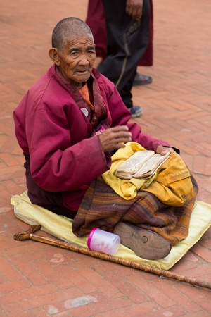 migrated: NEPAL, KATHMANDU, APRIL 21: unidentified Tibetan monk reading a old tibetan manuscript in front of the Boudhanath Stupa. Since 2008, most of the remaining monks have migrated to Kathmandu, Nepal 2013.