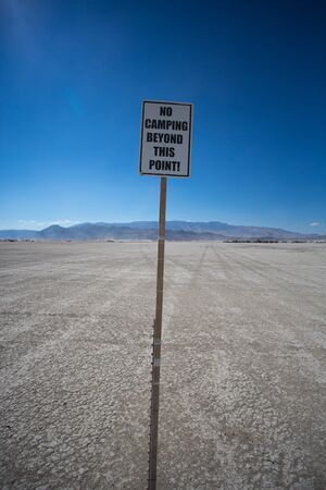 beyond: No camping beyond this point, interdiction sign in the dessert, Nevada during a public event Stock Photo