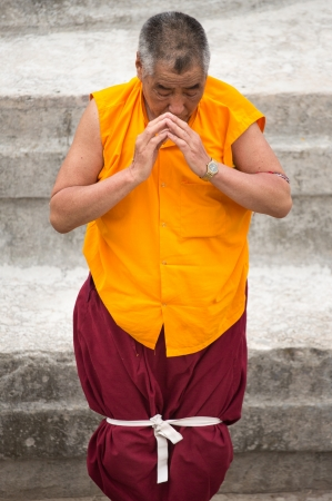migrated: NEPAL, KATHMANDU, APRIL 21: unidentified Tibetan monk praying at the Boudhanath Stupa. Since 2008, most of the remaining monks have migrated to Kathmandu, Nepal 2013. Editorial