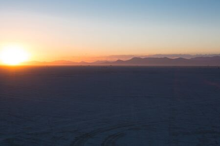 Black rock desert playa with streak of sunlight on horizon during Burning Man 2012 photo