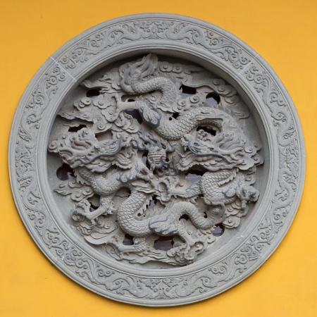 antiquary: Ventana adornada con el drag�n en una pared amarilla de un templo en Hanghzou, China, 2013