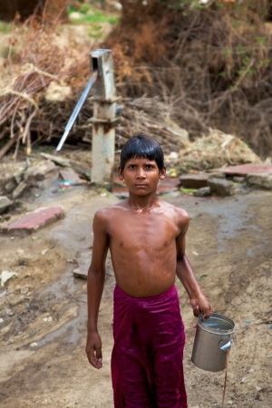 water sources: AGRA, INDIA, JULI 18: unidentified young boy carrying water at the water pump. Indians huge and growing population is putting a severe strain on all of the countrys natural resources. Most water sources are contaminated by sewage and agricultural runoff.