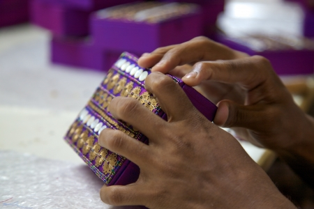 socioeconomic: Close-up of hands working on a purple box, a fair trade product made by artisans in Agra in the north of India, 2013.