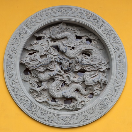 antiquary: Ornamented window with dragon on a yellow wall of a temple in Hanghzou, China, 2013