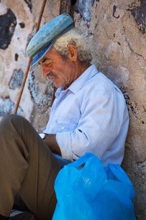 SANTORINI, GREECE, JULY 20: unidentified old man sitting quietly against a wall and protecting himself from the sun in Oia Santorini town, Greece, 2013. Editorial