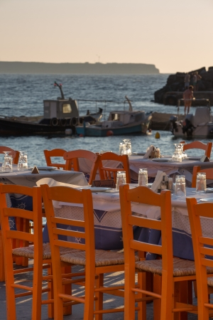 Oia fisher port restaurant and fisher boats in the background, Santorini, Greece  photo
