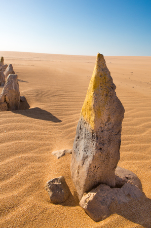 Yellow painted stone standing in the desert of Punta Gallinas against a blue sky, La Guajira, Colombia 2014. photo