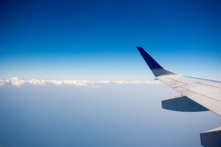 airplane window: View of jet plane wing with crystal blue sky in the background and clouds with copy space.