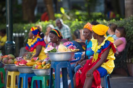 카르타헤나, 콜롬비아 1 월 11 알 수없는 여성이 앉아 및 판매 과일 카르타헤나의 오래 된 도시 및 2014년 1월 11일, 콜롬비아의 전통 옷을 입고