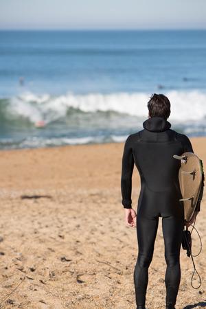 젊은 매력적인 서퍼 남자 비아리츠에서 휴가에 화창한 날 동안 대서양에서 찾고있는 동안 해변에 서 서 그의 서핑 보드를 들고.