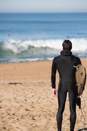 Young attractive surfer man standing on a beach and carrying his surfing board while looking at the Atlantic Ocean during a sunny day on vacation in Biarritz.