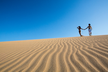 PUNTA GALLINAS, COLOMBIA, JANUARY 16: Beautiful and happy young couple walking in the sand. Punta Gallinas, La Guajira, Colombia 2014.