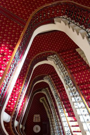 Massive red old classic staircase see from above in Bilbao hotel with view on comfortable lobby, Spain.
