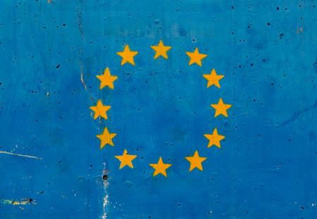 Yellow stars on blue concrete wall representing the European Union flag photo