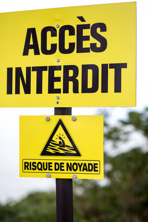 Yellow beach sign board saying no beach access, risk of drowning Biarritz, France photo