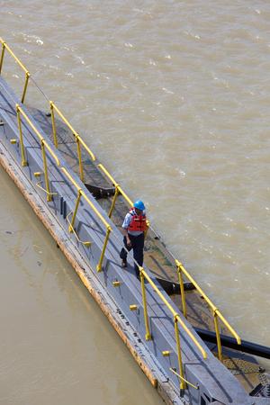 miraflores: MIRAFLORES LOCKS, PANAMA, JANUARY 03: Unidentified worker crossing the canal of Panama at Miraflores. On January 03 2014 in Panama City. Editorial