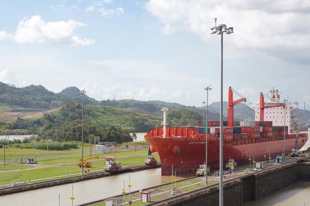 PANAMA CITY, PANAMA, JANUARY 3: Red Cap Stewart container ship entering in the basin of Miraflores Locks Panama Canal filling to raise a ship. Panama City, Panama 2014. Editorial