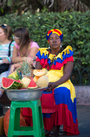 CARTAGENA, COLOMBIA, JANUARY 11: Unidentified woman sitting and selling fruits at the old city of Cartagena and dressed with the traditional clothes on January 11, 2014 , Colombia