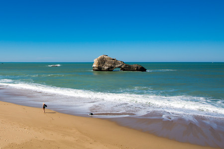 basque woman: Woman walking on the empty beach in Biarritz beach, rocks and blue ocean, Aquitaine, France