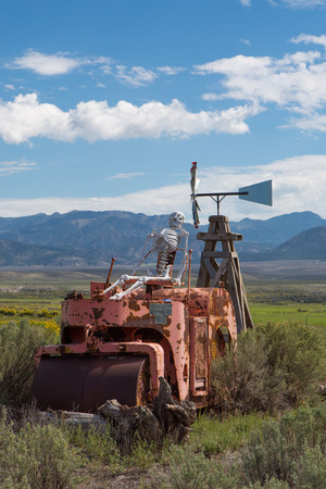Skeleton sitting on a vintage tractor in Utah with mountains in the background  photo
