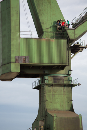GDANSK, POLAND, SEPTEMBER 18: Unidentified people working on top of an industrial massive crane in the Shipyards of Gdansk, Poland.