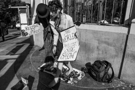 SAN FRANCISCO, CA, AUGUST 25  Unidentified couple performing in the street with strange message boards saying, the world smallest side show  The photo is black and white Editorial